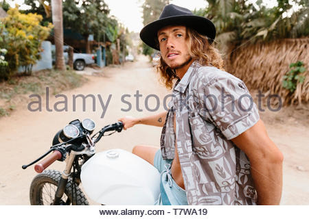 Portrait confident, cool young man riding motorcycle on dirt road, Mexico - Stock Photo