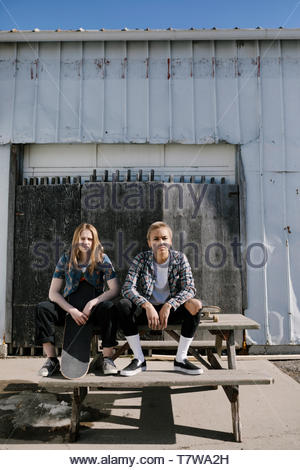 Portrait confident, cool young female skateboarders sitting on sunny picnic table - Stock Photo