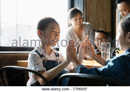 Sisters playing clapping game in restaurant - Stock Photo