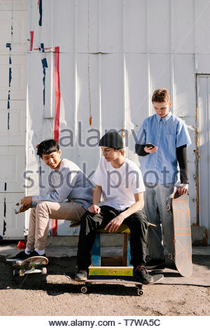 Teenage male skateboarders hanging out, using smart phone outdoors - Stock Photo