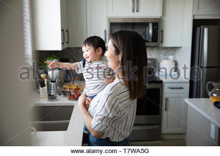 Mother and cute toddler daughter in kitchen - Stock Photo