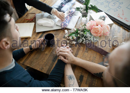 Affectionate male gay couple meeting with wedding planner - Stock Photo