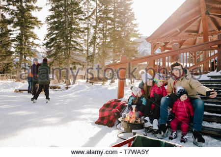 Family taking selfie, taking a break from ice skating on snowy steps - Stock Photo