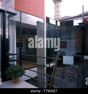 Exterior of an architectural house with metal banisters on balcony on the first floor - Stock Photo