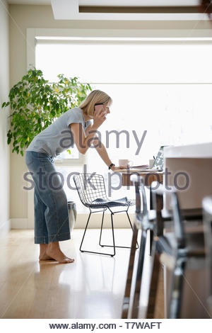 Woman working from home, talking on smart phone at laptop in dining room - Stock Photo