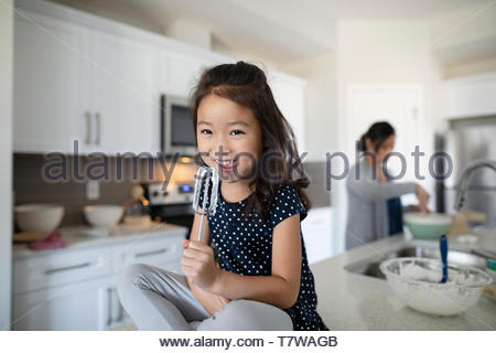 Portrait cute girl licking frosting from beater in kitchen - Stock Photo