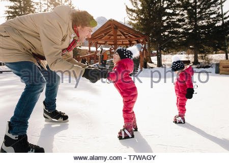 Father and toddler daughter ice skating on frozen pond - Stock Photo
