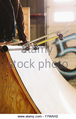 Friends with skateboards at top of ramp at indoor skate park - Stock Photo