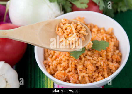 Mexican -style rice in white bowl with close-up of wooden spoonful of rice in foreground, ingredients set against green background - Stock Photo