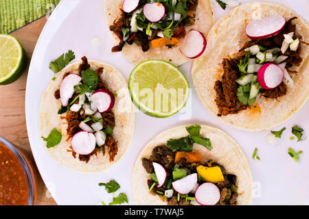 Four open -faced tacos on white plate - Stock Photo