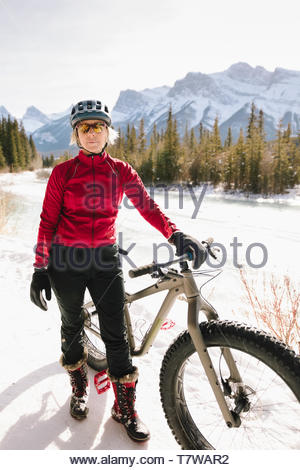 Portrait confident woman fat biking in snow - Stock Photo