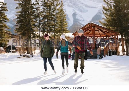 Senior couple and daughter ice skating on frozen pond - Stock Photo
