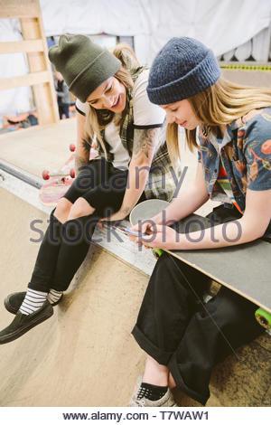 Female skateboarders using smart phone at indoor skate park - Stock Photo