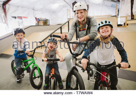 Portrait happy mother and children on bmx bikes at indoor skate park - Stock Photo