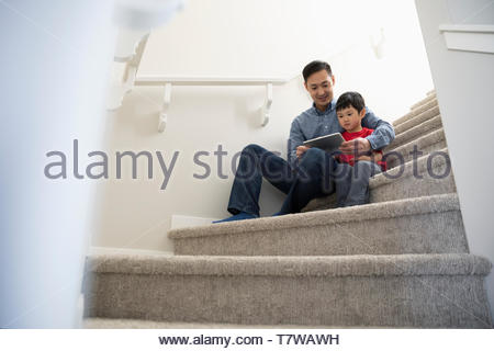 Father and son using digital tablet on stairs - Stock Photo