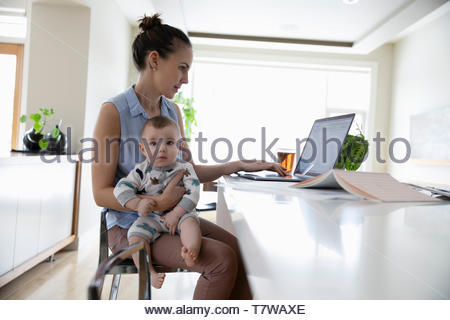 Mother with baby working at home - Stock Photo