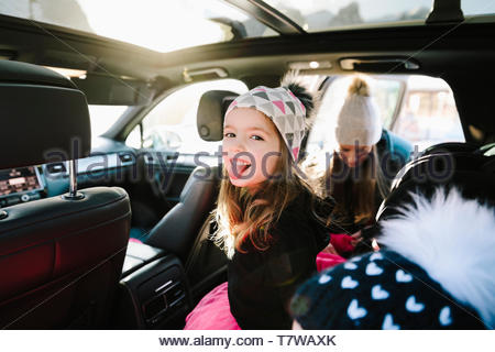 Portrait playful girl in car sticking out tongue - Stock Photo
