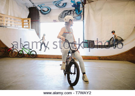 Mother on bmx bike watching children playing on ramp at indoor skate park - Stock Photo