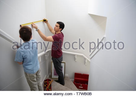 Father and son using tape measure, measuring wall above stairs - Stock Photo