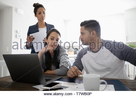 Financial advisor meeting with couple at laptop in dining room - Stock Photo
