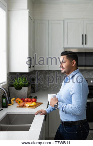 Thoughtful man drinking coffee and looking out kitchen window - Stock Photo