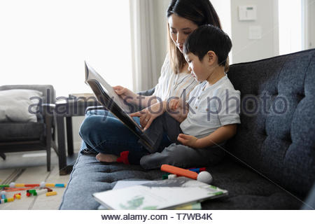 Mother and son reading book on living room sofa - Stock Photo