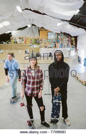 Portrait confident, cool skateboarder friends at indoor skate park - Stock Photo