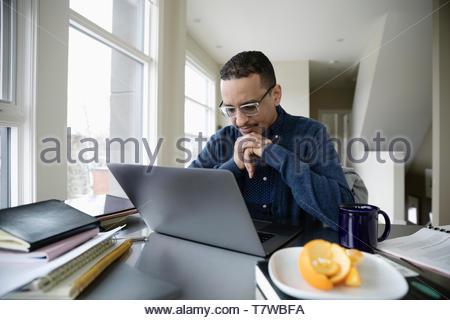 Man working from home, using laptop - Stock Photo
