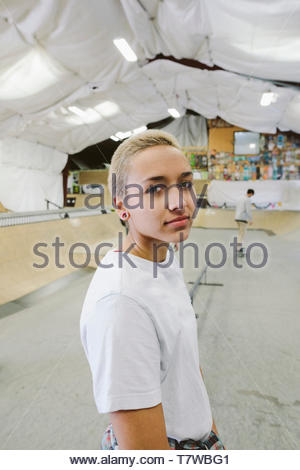 Portrait confident, cool young woman at indoor skate park - Stock Photo
