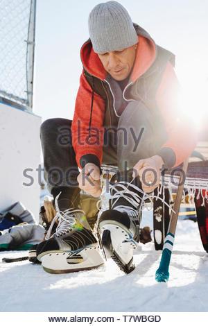Man tying ice skates in snow - Stock Photo
