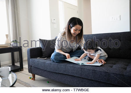 Mother and toddler daughter reading book on living room sofa - Stock Photo