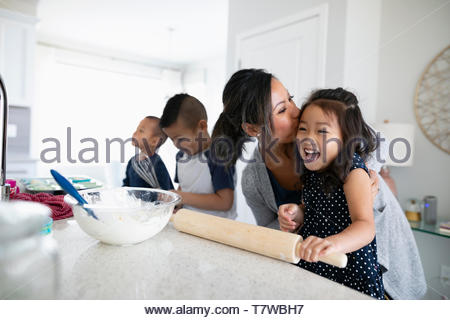 Affectionate mother and children baking in kitchen - Stock Photo