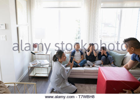 Parents surprising children with gift in living room - Stock Photo