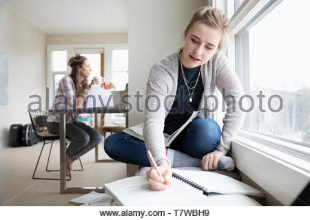 Teenage girl doing homework while mother works in background - Stock Photo