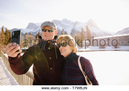 Smiling senior couple taking selfie on frozen pond - Stock Photo