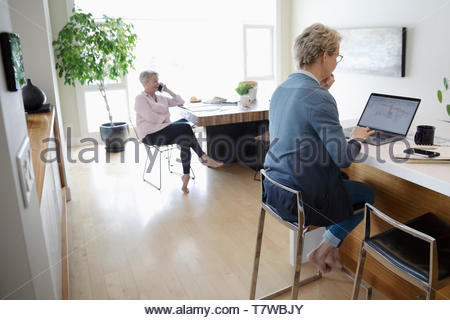 Woman using laptop in kitchen while senior mother talks on smart phone at table - Stock Photo