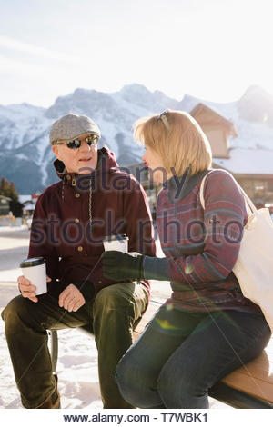 Senior couple talking and drinking coffee on sunny bench with snowy mountains in background - Stock Photo
