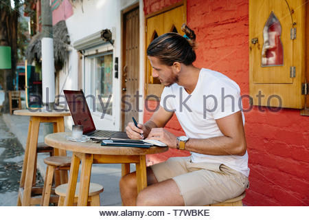 Young male tourist working at laptop at sidewalk cafe, Mexico - Stock Photo