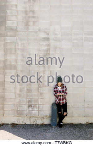 Young female skateboarder using smart phone against concrete wall - Stock Photo