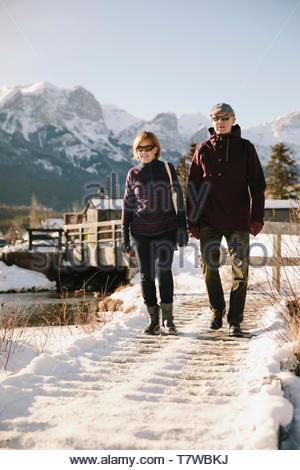 Senior couple walking along snowy path below mountains - Stock Photo