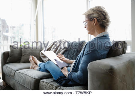 Mature woman using digital tablet on living room sofa - Stock Photo
