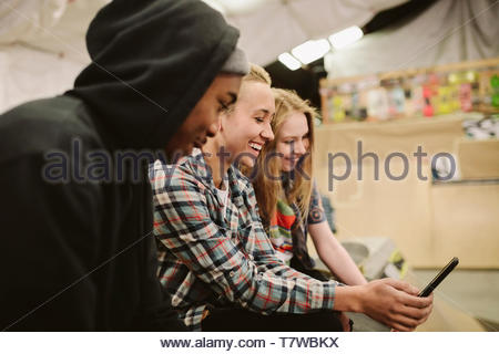 Happy teenage friends hanging out at indoor skate park, using smart phone - Stock Photo