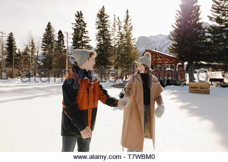 Affectionate young couple holding hands and ice skating on sunny, frozen pond - Stock Photo