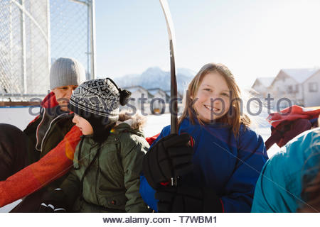Portrait smiling boy playing outdoor ice hockey with family - Stock Photo