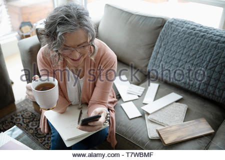 Senior female interior designer working on living room sofa - Stock Photo