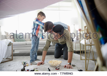 Father and sons playing in living room - Stock Photo
