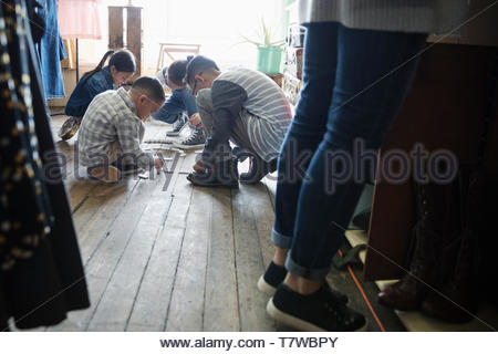 Kids playing dominos on shop floor - Stock Photo