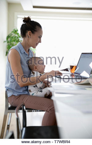 Mother with baby working from home, using laptop in kitchen - Stock Photo
