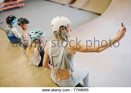 Mother and children taking selfie on ramp at indoor skate park - Stock Photo