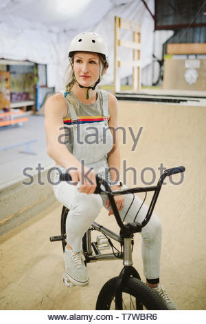 Woman on bmx bike at indoor skate park - Stock Photo